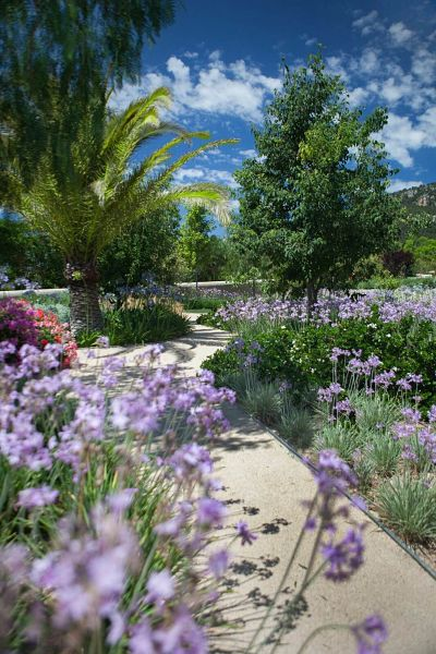 Un camino entre los jardines de un Hotel con historia en Mallorca. El camino serpentea entre flores de colores y el cielo azul en Castell son Claret.