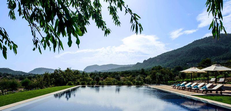 Visión frontal del Hotel Castell Son Claret en Mallorca con cielo azul, flores y la naturaleza de la Serra de Tramuntana a su alrededor.
