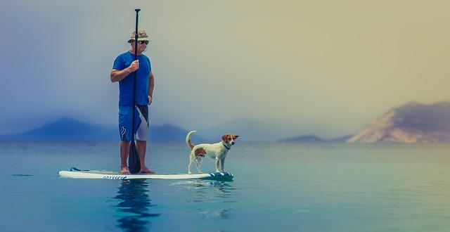Aufstehen beim Paddeln auf Mallorca - älterer Mann mit kleinem Hund an Bord.