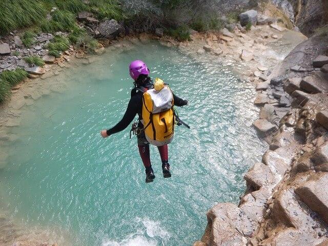 Frau in Canyoning-Ausrüstung springt auf Mallorca ins Wasser