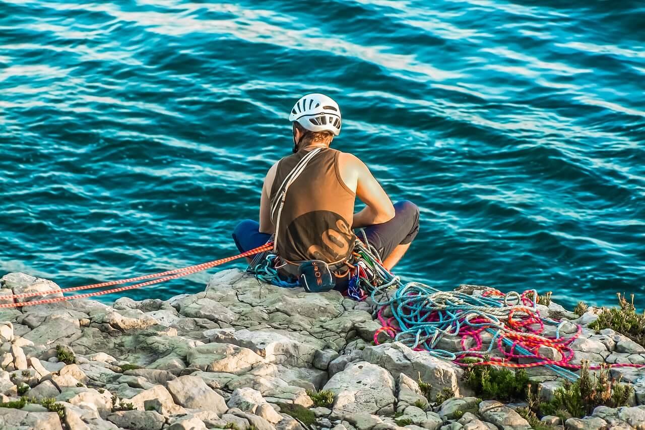 Bergsteiger mit Schutzausrüstung sitzt auf einem Stein.