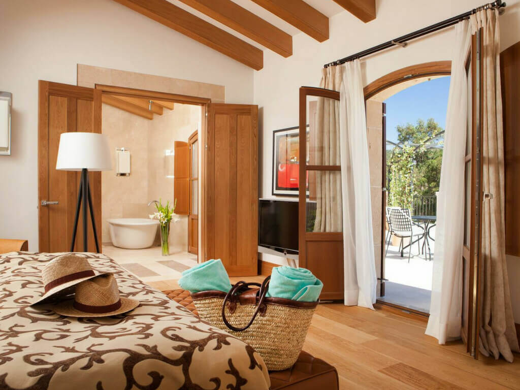 The spacious living room of a Terrace-Demi-Suite in Castell Son Claret with its own terrace. In the background you can see the bright bathroom with bathtub.