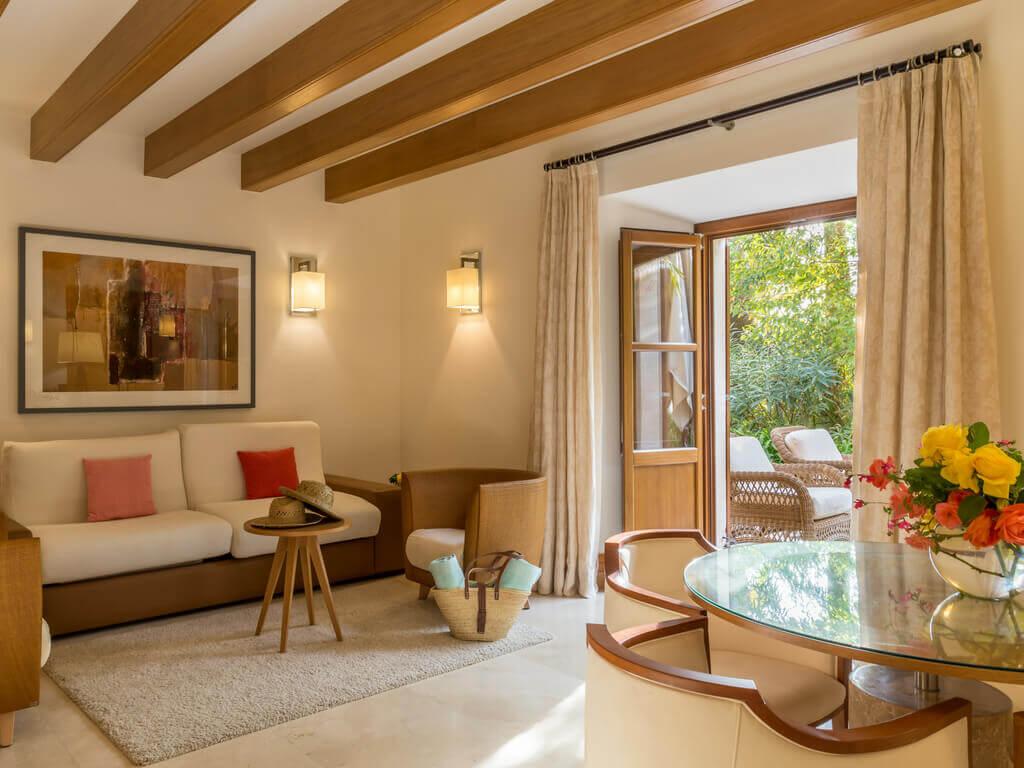 Der, mit hellen Holz und in Pastelltönen gestaltete, Wohnbereich einer Suite im Castell Son Claret mit einem runden Glastisch und einer Sitzgruppe aus Leder