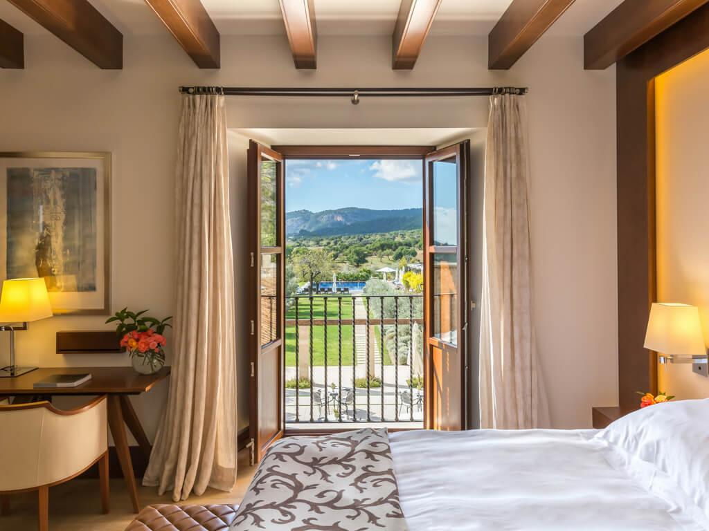 In einem Zimmer im Castell Son Claret ist die Balkontür geöffnet, wodurch man direkt in den Hotelgarten und auf den Pool schauen kann