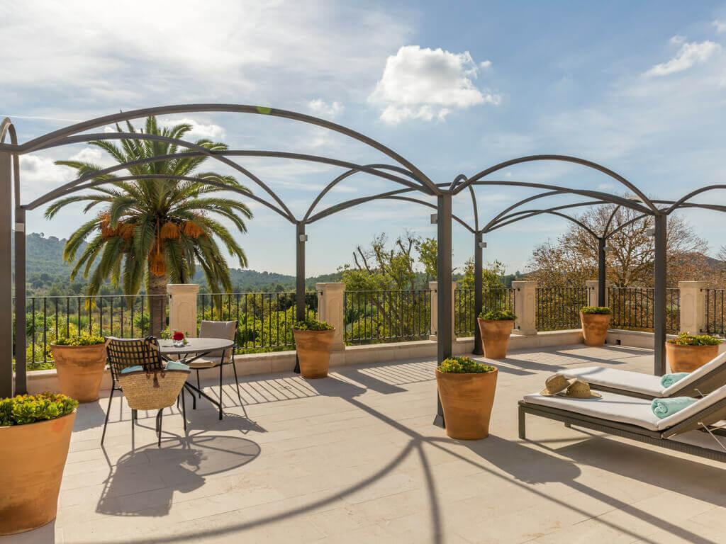 Die große Terrasse im Castell Son Claret mit einer kleinen Sitzgruppe, zwei Liegestühlen, Blümentöpfen und einem fantastischen Ausblick auf die Landschaft Mallorcas
