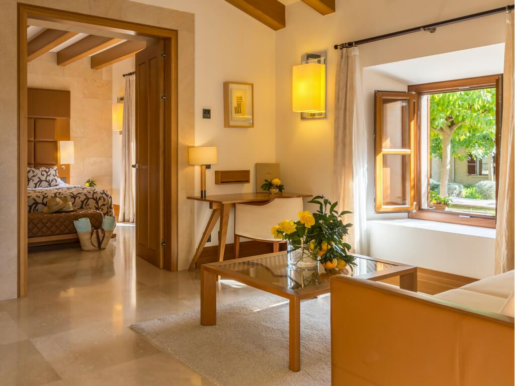 Der sonnige Wohnbereich eines Hotelzimmers im Castell Son Claret mit einem kleinen Schreibtisch und einer Couch - durch eine Tür blickt man ins Schlafzimmer