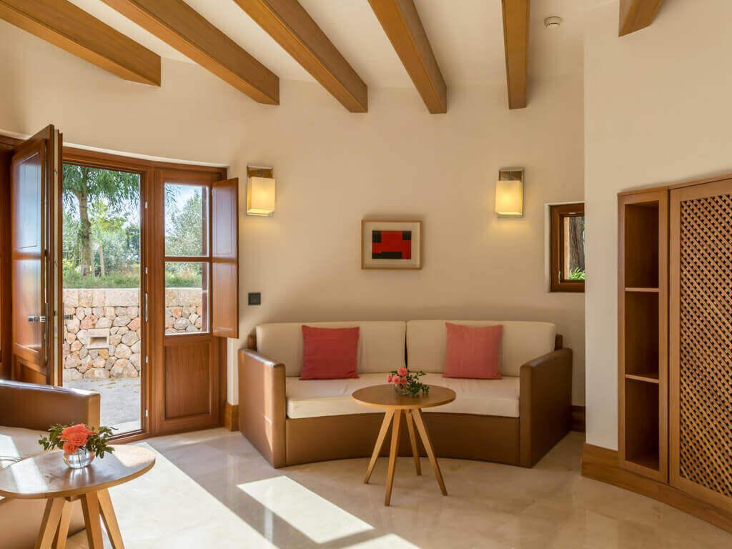 Durch die Terrassentür einer Suite scheint die Sonne hell in den Wohnbereich, in dem eine großzügige Couch und ein Beistelltisch steht