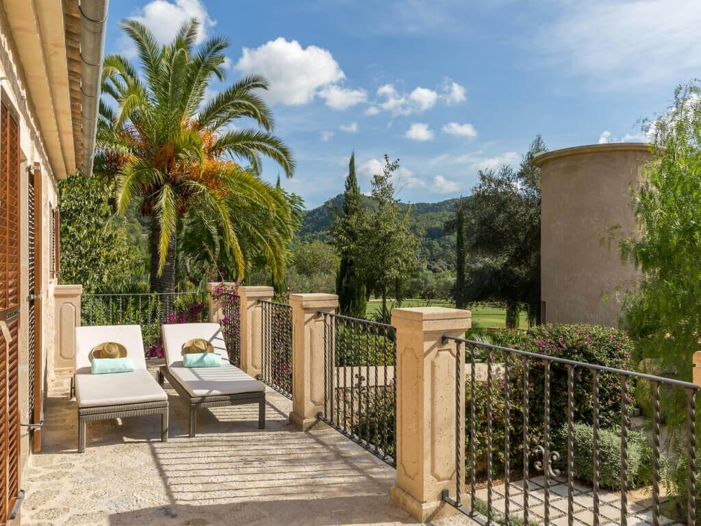 Ein großzügiger Balkon einer Suite im Castell Son Claret, auf der zwei Liegestühle stehen - im Hintergrund ist der Hotelgarten mit Palmen zu sehen