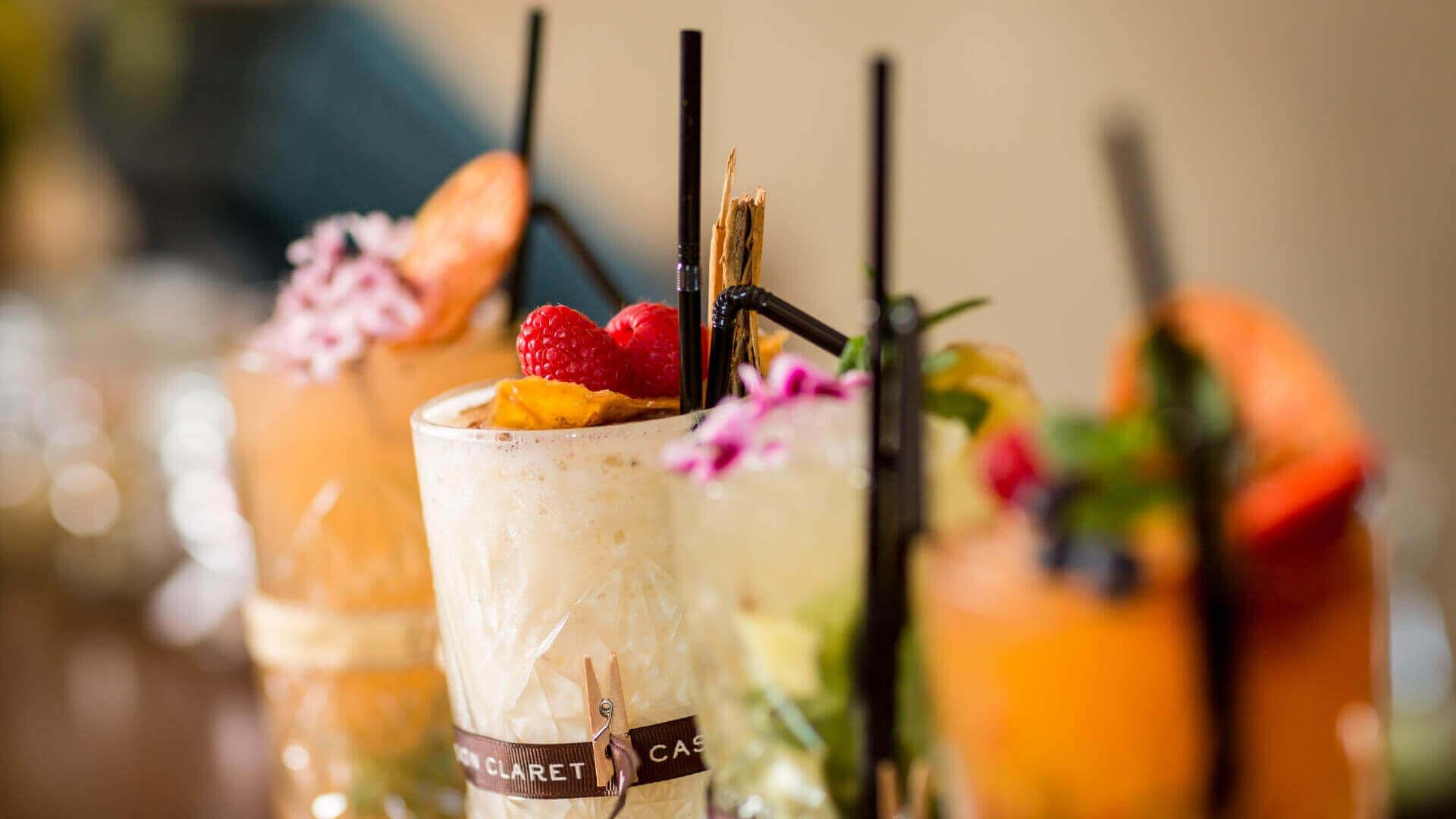 An der Bar im Castell Son Claret gibt es vier verschiedene Cocktails, die jeweils bunt dekoriert und auf einer Holzscheibe serviert werden.