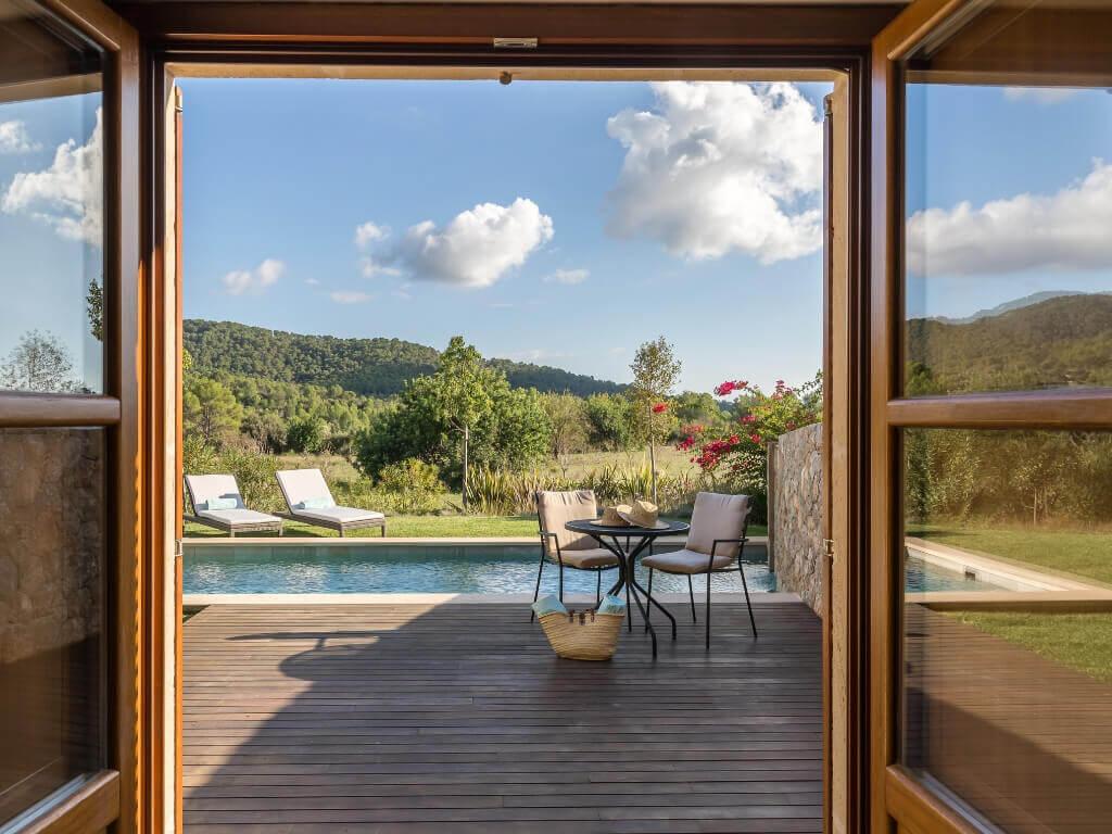 Der Blick auf die Terrasse und den Pool einer Pool-Suite im Castell Son Claret durch die Terrassentür eines Zimmers
