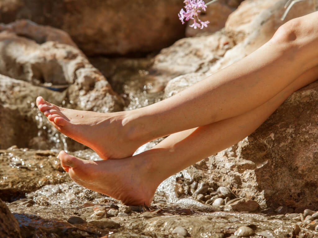 A young woman sits barefoot on a rock near the Castell Son Claret - holding a flower in her hand
