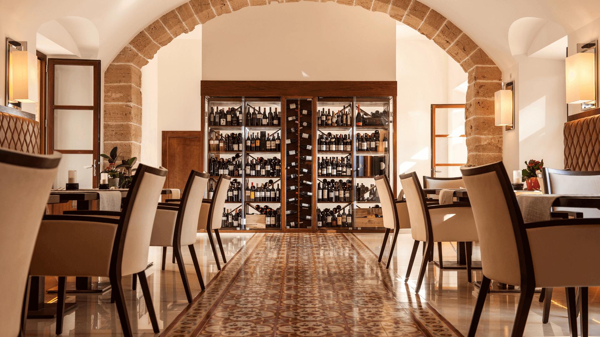 Hinter einem gemauerten Torbogens steht im Restaurant Olivera im Castell Son Claret ein großer, gefüllter Weinschrank