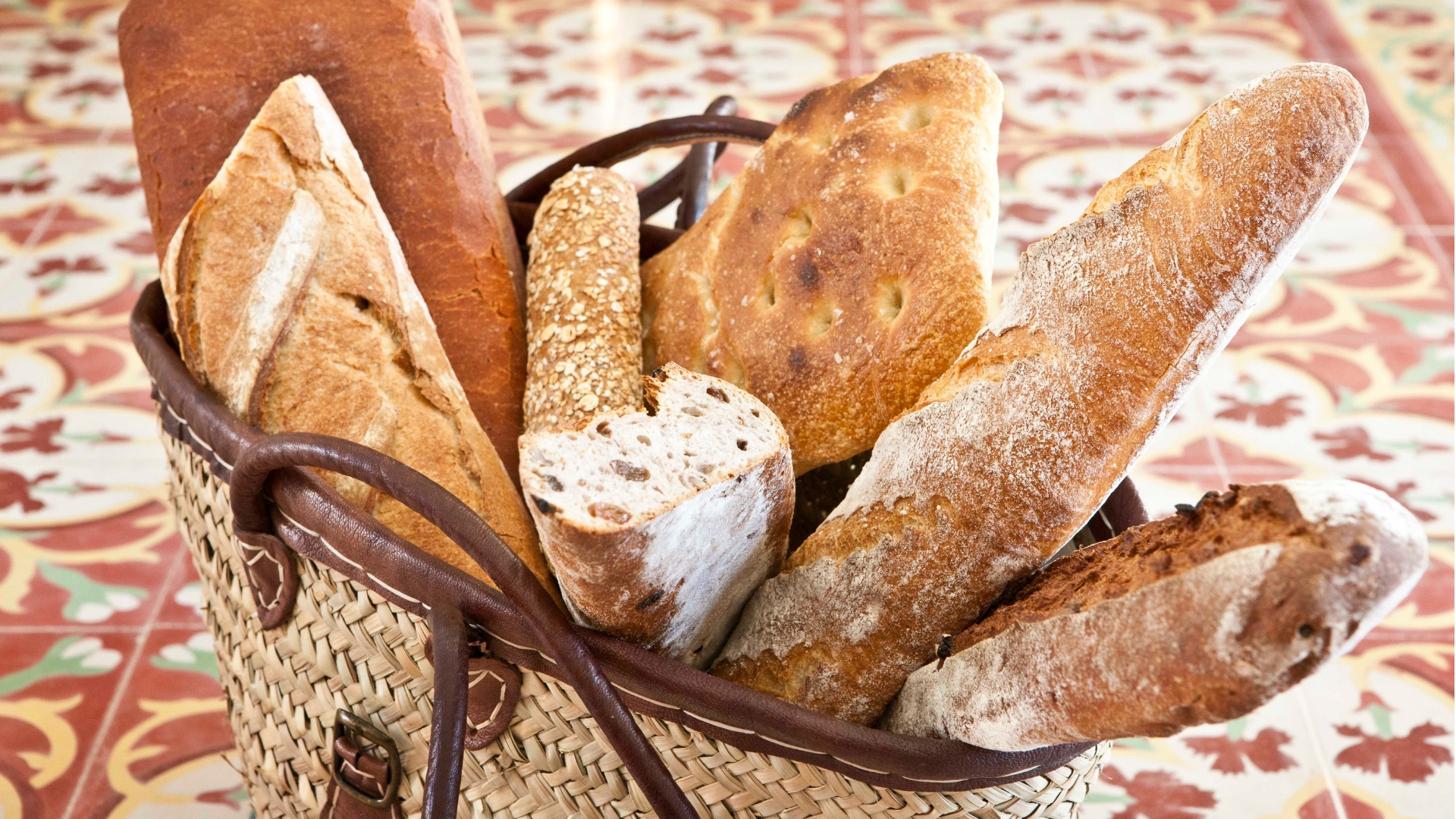 A large basket of different breads and baguettes stands on the tiled floor of the Olivera Restaurant in Castell Son Claret.